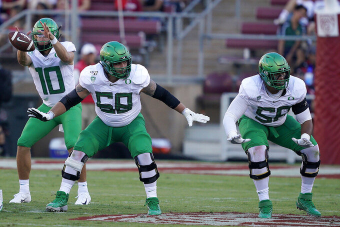 FILE - In this Sept. 21, 2019, file photo, Oregon offensive linemen Shane Lemieux (68) and Penei Sewell, right, block for quarterback Justin Herbert (10) against Stanford during the first half of an NCAA college football game in Stanford, Calif. The acquisition of Sam Darnold via trade earlier this month has given the Carolina Panthers more options with the No. 8 pick in the NFL draft. Carolina's most pressing need entering the draft is at left tackle, a position they have failed to solidify over the last seven seasons. That means 6-foot-6, 330-pound Sewell and 6-foot-3, 305-pound Rashawn Slater from Northwestern could be in play if either is around at No. 8. (AP Photo/Tony Avelar, File)