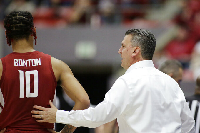 Washington State coach Kyle Smith, right, speaks with guard Isaac Bonton (10) during the second half of the teams NCAA college basketball game against Arizona in Pullman, Wash., Saturday, Feb. 1, 2020. Arizona won 66-49. (AP Photo/Young Kwak)
