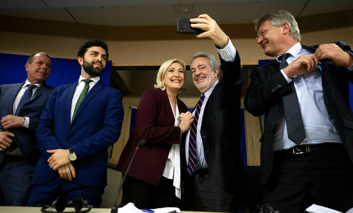 French far-right National Rally leader and MEP Marine Le Pen, center left, and Belgium's Vlaams Belang member and MEP Gerolf Annemans, center right, take a cellphone photo of themselves after attending a media conference to announce the formation of a new far-right European Parliament group at the European Parliament in Brussels, Thursday, June 13, 2019. (AP Photo/Virginia Mayo)