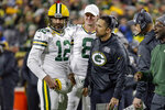 Green Bay Packers quarterback Aaron Rodgers (12) and head coach Matt LaFleur, third from left, talk during a timeout in the first half of an NFL football game against the Detroit Lions, Monday, Oct. 14, 2019, in Green Bay, Wis. (AP Photo/Mike Roemer)