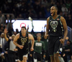 Milwaukee Bucks' Khris Middleton, right, reacts after making a three-point basket during the second half of an NBA basketball game against the Boston Celtics, Thursday, Feb. 21, 2019, in Milwaukee. (AP Photo/Aaron Gash)