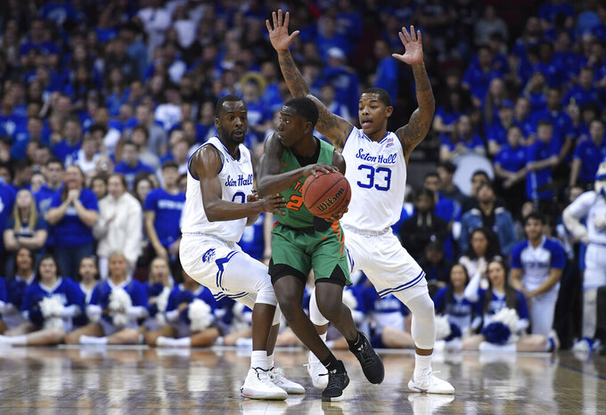 Florida A&M guard Kamron Reaves (2) looks to pass as Seton Hall guards Quincy McKnight (0) and Shavar Reynolds (33) defend during the second half of an NCAA college basketball game, Saturday, Nov. 23, 2019 in Newark, N.J. (AP Photo/Sarah Stier)