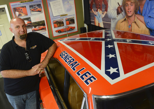 Volo Auto Museum owner and director Brian Grams poses with one of the museum's 1969 Dodge Chargers driven in the television series