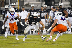 Central Florida running back Isaiah Bowser (5) looks for a way past Boise State safety Tyreque Jones (21) and linebacker Riley Whimpey (44) during the second half of an NCAA college football game Friday, Sept. 3, 2021, in Orlando, Fla. (AP Photo/John Raoux)