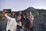 In this Tuesday, Aug. 6, 2019, photo, local tourists take a selfie with the background of Mount Merapi, in Yogyakarta, Indonesia. The Indonesian city of Yogyakarta and its hinterland are packed with tourist attractions, including Buddhist and Hindu temples of World Heritage. Yet many tourists still bypass the congested city and head to the relaxing beaches of Bali. Recently re-elected President Joko Widodo wants to change this dynamic by pushing ahead with creating