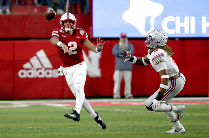 Nebraska quarterback Adrian Martinez (2) throws an interception while being pursued by Ohio State defensive end Chase Young, right, during the first half of an NCAA college football game in Lincoln, Neb., Saturday, Sept. 28, 2019. (AP Photo/Nati Harnik)