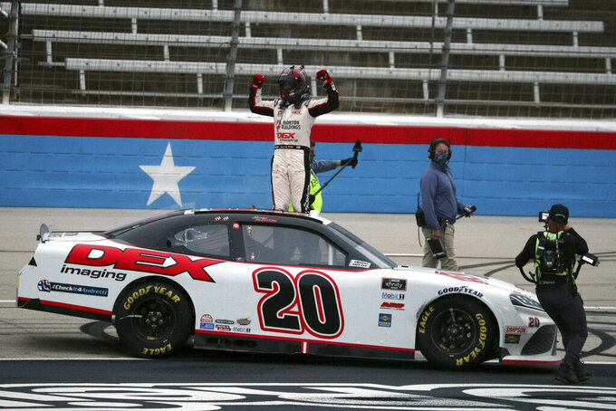 Harrison Burton (20) pumps his fists in the air after winning a NASCAR Xfinity Series auto race at Texas Motor Speedway in Fort Worth, Texas, Saturday Oct. 24, 2020. (AP Photo/Richard W. Rodriguez)