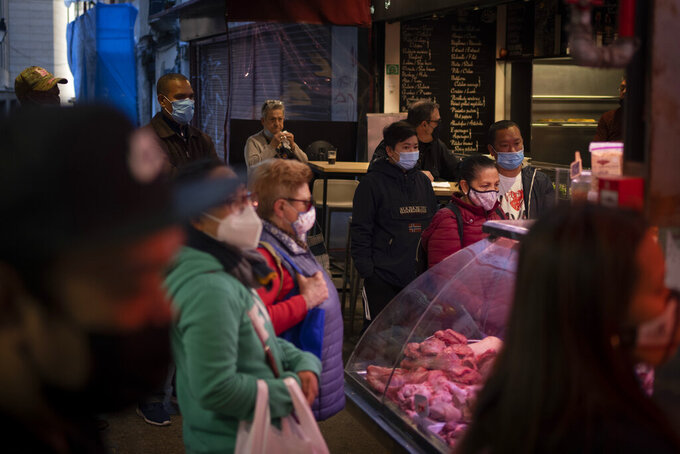 Customers wearing face masks wait to buy meat at a market in downtown Barcelona, Spain, Wednesday, May 5, 2021. (AP Photo/Emilio Morenatti)