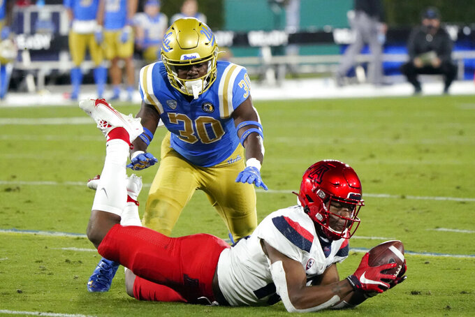 Arizona wide receiver Jamarye Joiner, bottom, makes catch in front of UCLA defensive back Elisha Guidry (30) during the second half of an NCAA college football game Saturday, Nov. 28, 2020, in Pasadena, Calif. (AP Photo/Marcio Jose Sanchez)
