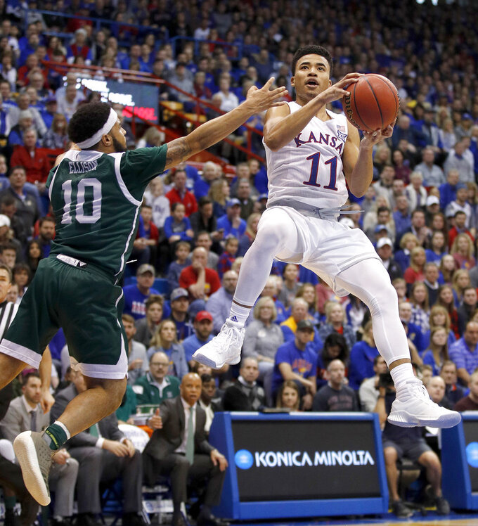 Kansas' Devon Dotson (11) shoots under pressure from Eastern Michigan's Malik Ellison (10) during the first half of an NCAA college basketball game Saturday, Dec. 29, 2018, in Lawrence, Kan. (AP Photo/Charlie Riedel)