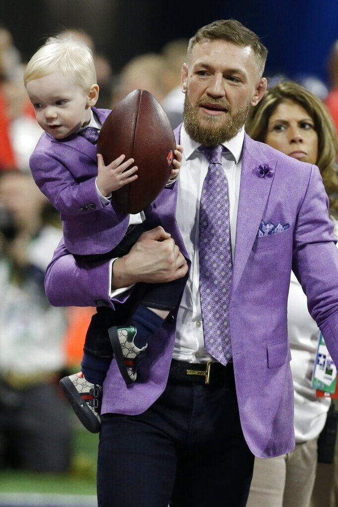 THIS CORRECTS FROM  CONNER TO CONOR: UFC Champion Conor McGregor holds his son Conor Jr. as he enters the field, before the NFL Super Bowl 53 football game between the Los Angeles Rams and the New England Patriots Sunday, Feb. 3, 2019, in Atlanta. (AP Photo/Mark Humphrey)