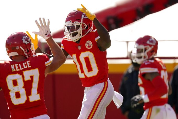 Kansas City Chiefs' Travis Kelce (87) and Tyreek Hill (10) celebrate a touchdown catch by Hill in the first half of an NFL football game against the New York Jets on Sunday, Nov. 1, 2020, in Kansas City, Mo. (AP Photo/Charlie Riedel)