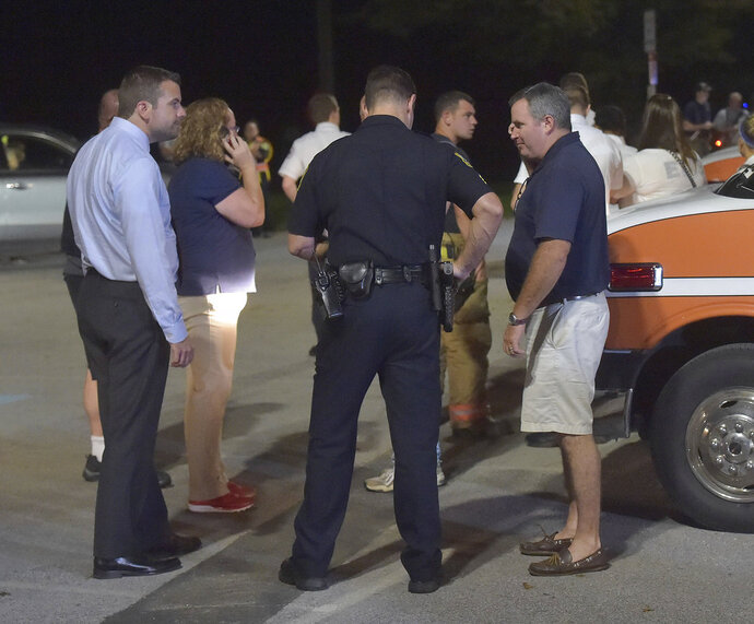 Police talk with family members at the staging area after a shooting at Bellingham Retirement Community on East Boot Road in East Goshen Township, Pa., Wednesday, Sept. 19, 2018. Authorities are searching for a man who they say shot at his ex-wife and then killed his parents at the retirement center. Chester County District Attorney Tom Hogan says authorities are looking for 59-year-old Bruce Rogal of Glenmoore. (Pete Bannan/Daily Local News via AP)