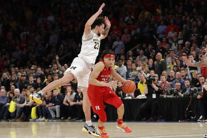Rutgers's Caleb McConnell (22) drives past Michigan's Brandon Johns Jr. (23) during the second half of an NCAA college basketball game Saturday, Feb. 1, 2020, in New York. Michigan won 69-63. (AP Photo/Frank Franklin II)