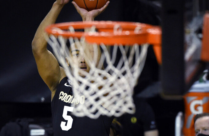 Colorado guard D'Shawn Schwartz (5) eyes the basket on a 3-point shot during the first half of the team's NCAA college basketball game against Oregon on Thursday, Feb. 18, 2021, in Eugene, Ore. (AP Photo/Andy Nelson)