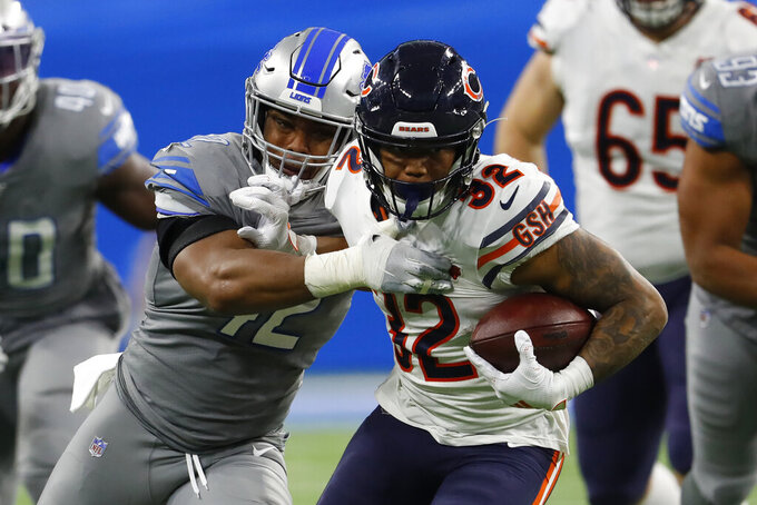 Chicago Bears running back David Montgomery (32) tries pulling away from Detroit Lions outside linebacker Devon Kennard (42) during the second half of an NFL football game, Thursday, Nov. 28, 2019, in Detroit. (AP Photo/Paul Sancya)