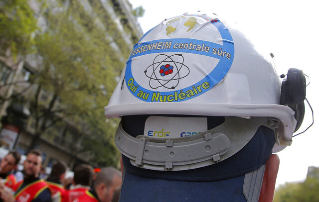 FILE - In this file photo dated Thursday, April 6, 2017, a sticker is photographed on a helmet of an employee of Fessenheim's nuclear power plant opposing the closure, during a protest outside the EDF headquarters in Paris, France. A statement released Wednesday Feb. 19, 2020, that Fessenehim will close one of its reactors on upcoming Saturday, as the first phase of a shut-down at the plant.  Sticker on helmet reads,