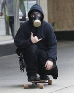 A skateboarder makes the Hang Loose sign as he rolls a sidewalk in Wilkes-Barre Pa., Tuesday, March 24, 2020 while wearing a gas mask. (Dave Scherbenco/The Citizens' Voice via AP)