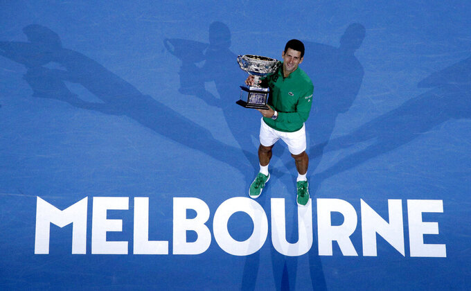 FILE - In this Monday, Feb. 3, 2020 file photo, Serbia's Novak Djokovic holds the Norman Brookes Challenge Cup after defeating Austria's Dominic Thiem in the men's singles final of the Australian Open tennis championship in Melbourne, Australia. The 2021 Australian Open will begin three weeks later than planned. That is part of a pandemic-altered 2021 tennis calendar released by the men's professional tour Wednesday, Dec. 16, 2020.  (AP Photo/Andy Wong, File)