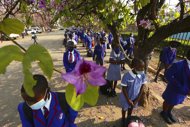 Schoolchildren wait to enter their school in Harare, Zimbabwe, Monday Sept, 28, 2020. Zimbabwe schools have reopened in phases, but with smaller number of pupils, more teachers and other related measures to enable children to resume their education without the risk of a spike in COVID-19 infections. (AP Photo/Tsvangirayi Mukwazhi)