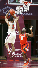 Virginia Tech's Wabissa Bede (3) scores over Clemson's John Newman III 15 in the second half of an NCAA  college basketball game in Blacksburg Va., Tuesday, Dec. 15, 2020.  (Matt Gentry/The Roanoke Times via AP, Pool)