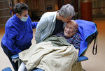 FILE - Melvin Goldstein, 90, smiles as his daughter Barbara Goldstein gives him a kiss on the head during their first in-person, indoor family visit inside the Hebrew Home at Riverdale, Sunday, March 28, 2021, in the Bronx borough of New York. A focus on the elderly at the start of the nation's vaccination campaign helped protect nursing homes that were ravaged at the height of the U.S. coronavirus outbreak, but they are far from in the clear. New outbreaks, often traced to infected staff members, are still occurring in long-term care centers across the country, causing continued havoc for visitation policies. (AP Photo/Kathy Willens)