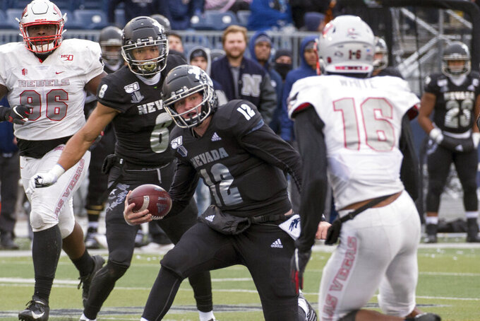 FILE - In this Nov. 30, 2019, file photo, Nevada quarterback Carson Strong (12) cuts back as UNLV linebacker Javin White (16) closes in during the second half of an NCAA college football game in Reno, Nev. The Las Vegas Raiders were the first team to play inside Allegiant Stadium. But the UNLV Rebels will be the first team to play with fans inside the $2 billion dollar venue, when they host in-state rival Nevada on Saturday, Oct. 31, 2020. (AP Photo/Tom R. Smedes, File)