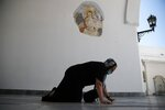 An elderly woman crawls as she enters the entrance of the Holy Church of Panagia of Tinos, on the Aegean island of Tinos, Greece, on Thursday, Aug. 13, 2020. For nearly 200 years, Greek Orthodox faithful have flocked to Tinos for the August 15 feast day of the Assumption of the Virgin Mary, the most revered religious holiday in the Orthodox calendar after Easter. But this year there was no procession, the ceremony _ like so many lives across the globe _ upended by the coronavirus pandemic. (AP Photo/Thanassis Stavrakis)