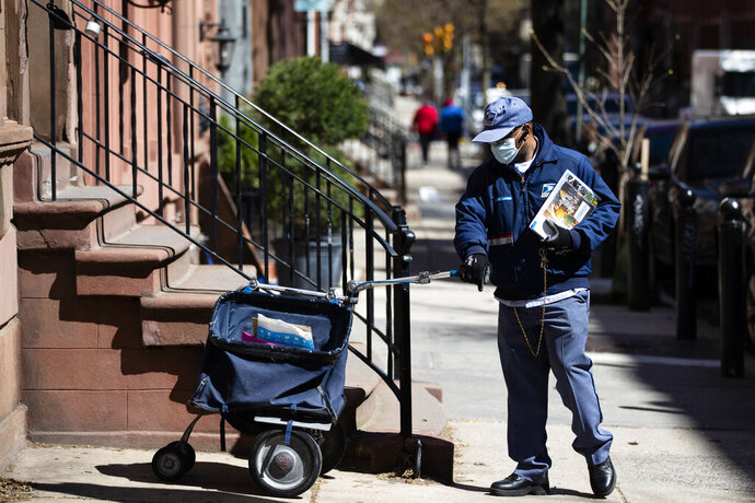 A United States Postal worker makes a delivery with gloves and a mask in Philadelphia, Thursday, April 2, 2020. The U.S. Postal Service is keeping post offices open but ensuring customers stay at least 6 feet (2 meters) apart. The agency said it is following guidance from public health experts, although there is no indication that the new coronavirus COVID-19 is being spread through the mail. (AP Photo/Matt Rourke)