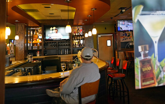 A customer sits at a bar, Tuesday, Nov. 10, 2020, at a Bloomington, Minn., restaurant. Minnesota Gov. Tim Walz announced restrictions that bars and restaurants will be required to end dine-in service between 10 p.m. and 4 a.m., beginning Friday in an effort to slow the spread of the COVID-19 virus. (AP Photo/Jim Mone)