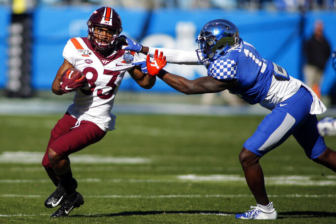 Virginia Tech wide receiver Tayvion Robinson, left, fights for yardage against a Kentucky defender during the first half of the Belk Bowl NCAA college football game in Charlotte, N.C., Tuesday, Dec. 31, 2019. (AP Photo/Nell Redmond)