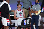 Washington Wizards' Moritz Wagner (21) smiles as he sits on the bench during a time out after Milwaukee Bucks' Giannis Antetokounmpo was ejected during the first half of an NBA basketball game, Tuesday, Aug. 11, 2020, in Lake Buena Vista, Fla. (AP Photo/Ashley Landis, Pool)