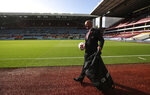An Aston Villa member of staff wearing a mask holds a soccer ball as he walks by the pitch ahead of the English Premier League soccer match between Aston Villa and Southampton at Villa Park in Birmingham, England, Sunday, Nov. 1, 2020. The British Prime Minister Boris Johnson announced Saturday night that England will have further restrictive measures to combat the coronavirus pandemic starting Thursday, though the Premier league and other elite sport would continue. (Nick Potts via AP)