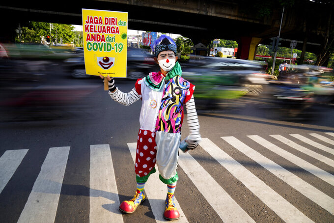 """A clown from a group called """"Aku Badut Indonesia"""" or """"I am an Indonesian Clown"""" holds up a poster during an awareness campaign calling for people to always wear their masks to curb the spread of coronavirus, at a busy intersection in Jakarta, Indonesia, Monday, July 12, 2021. The world's fourth most populous country is battling an explosion of COVID-19 cases that have strained hospitals on the main island of Java. Writings on the poster read """"Keep yourself and your family safe from COVID-19"""". (AP Photo/Dita Alangkara)"""