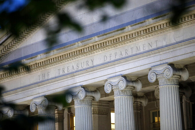 FILIE - This June 6, 2019, file photo shows the U.S. Treasury Department building at dusk in Washington. The President's Working Group on Financial Markets, led by the Treasury Department, issued a report Tuesday, Dec. 22, 2020, which said that the flight to safety triggered by the coronavirus pandemic last spring pointed to the need for reforms that will make money market funds less vulnerable to investors rushing to withdraw their funds. (AP Photo/Patrick Semansky, File)