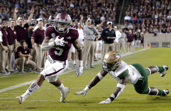 Texas A&M running back Trayveon Williams (5) dodges the tackle attempt by UAB linebacker Chris Woolbright, right, to score during the first half of an NCAA college football game Saturday, Nov. 17, 2018, in College Station, Texas. (AP Photo/Michael Wyke)