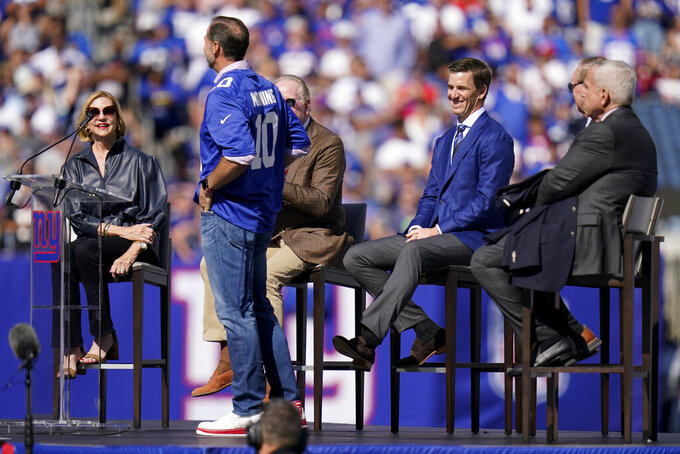 Former New York Giants quarterback Eli Manning, center right, smiles during a ceremony to retire his jersey number 10 and honor his tenure with the team during half-time in an NFL football game against the Atlanta Falcons, Sunday, Sept. 26, 2021, in East Rutherford, N.J. (AP Photo/Seth Wenig)