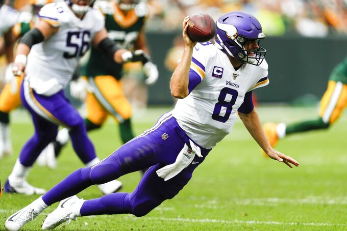 Minnesota Vikings' Kirk Cousins throws as he falls during the second half of an NFL football game against the Green Bay Packers Sunday, Sept. 15, 2019, in Green Bay, Wis. (AP Photo/Matt Ludtke)