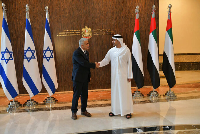 In this photo made available by the Israeli Government Press Office, Israeli Foreign Minister Yair Lapid shakes hands with United Arab Emirates Foreign Minister Sheikh Abdullah bin Zayed al-Nahyanin Abu Dhabi, United Arab Emirates, Tuesday, June 29, 2021. Lapid kicked off the highest-level visit by an Israeli official to the UAE on Tuesday, nine months after the two established relations in a deal brokered by the United States. (Shlomi Amsalem/Government Press Office via AP)