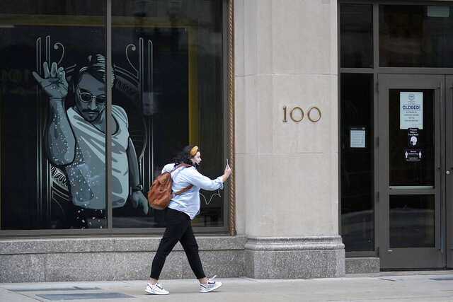 A passer-by uses a mobile device near a window featuring a likeness, left, of chef and social media star known as Salt Bae outside the Nusr-Et Boston restaurant, Tuesday, Sept. 29, 2020, in Boston. The restaurant opened by the Turkish restaurateur, whose real name is Nusret Gökçe, was ordered closed Sunday, Sept. 27, because officials said it posed a