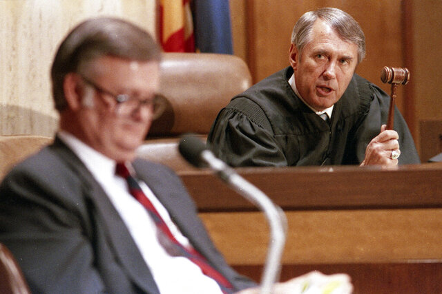 FILE - In this March 29, 1988, file photo, Arizona Supreme Court Chief Justice Frank X. Gordon Jr., right, waves his gavel at the defense's expert witness, attorney Robert L'Ecuyer, as Gordon threatened him with contempt of court during the impeachment trial of Arizona Gov. Evan Mecham in Phoenix. Gordon, who presided over the 1988 impeachment trial that resulted in the removal of Gov. Mecham, died Monday, Jan. 6, 2020, the state high court said in an statement Thursday, Jan. .9, 2020. He was 90. (AP Photo/Jeff Robbins, Pool, File)