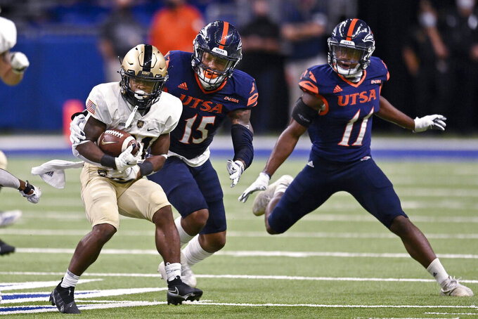 Army's Tyrell Robinson, left, attempts to evade UTSA's Trevor Harmanson (15) and Kelechi Nwachuku during an NCAA college football game on Saturday, Oct. 17, 2020, in San Antonio, Texas. (AP Photo/Darren Abate)