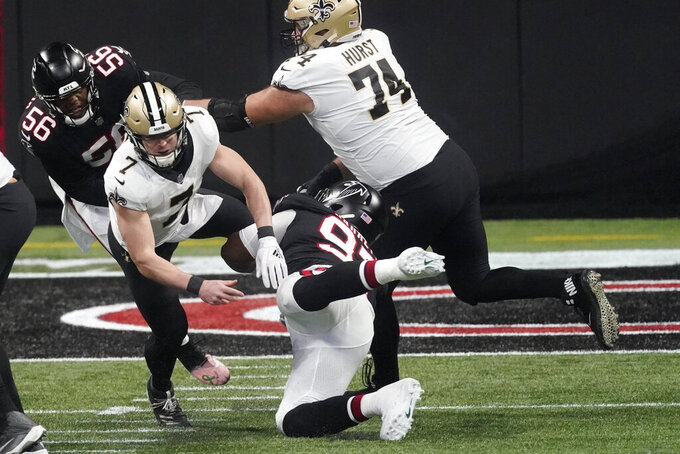 New Orleans Saints quarterback Taysom Hill (7) is hit by Atlanta Falcons defensive tackle Grady Jarrett (97) during the first half of an NFL football game, Sunday, Dec. 6, 2020, in Atlanta. Jarrett drew a penalty on the play. (AP Photo/John Bazemore)