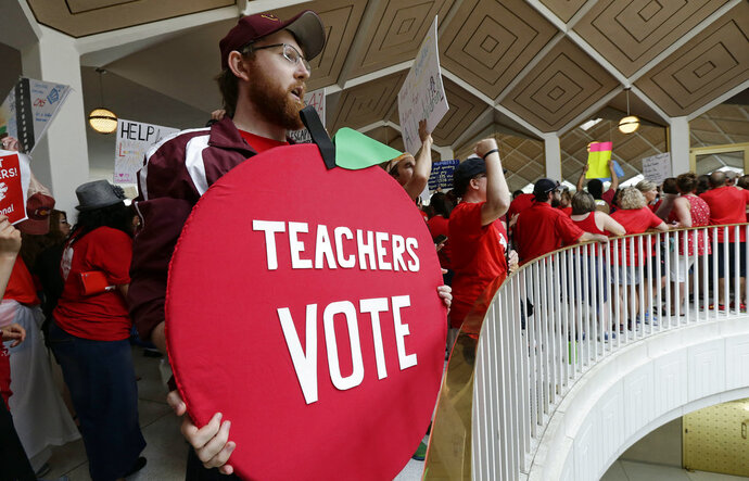 Kevin Poirier, an educator from West Charlotte school gathers with other educators during a teachers rally at the General Assembly in Raleigh, N.C., Wednesday, May 16, 2018. Thousands of teachers rallied the state capital seeking a political showdown over wages and funding for public school classrooms. (AP Photo/Gerry Broome)