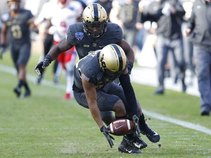 Army defensive back Cameron Jones (20) picks up a fumble by Houston quarterback Clayton Tune during the first half of Armed Forces Bowl NCAA college football game Saturday, Dec. 22, 2018, in Fort Worth, Texas. Jones scored on the play. (AP Photo/Jim Cowsert)