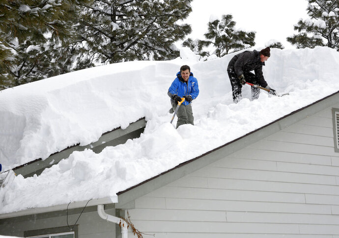Homeowner Kevin Ireland, right, and Tommy Tokarczyk clear several feet of snow off the roof in the Durango West I Subdivision Friday, Feb. 22 2019, west of Durango Colo. Southwest Colorado has been hit with several feet of snow thanks to recents winter storms. (Jerry McBride/The Durango Herald via AP)