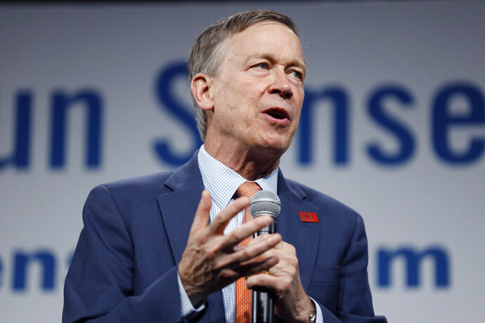 FILE - In this Aug. 10, 2019, file photo, then Democratic presidential candidate former Colorado Gov. John Hickenlooper speaks at the Presidential Gun Sense Forum in Des Moines, Iowa. The Colorado Ethics Commission is releasing an investigation into John Hickenlooper's use of private planes while governor. A Republican critic filed a complaint alleging Hickenlooper had improperly traveled on private flights during his administration. (AP Photo/Charlie Neibergall, File)