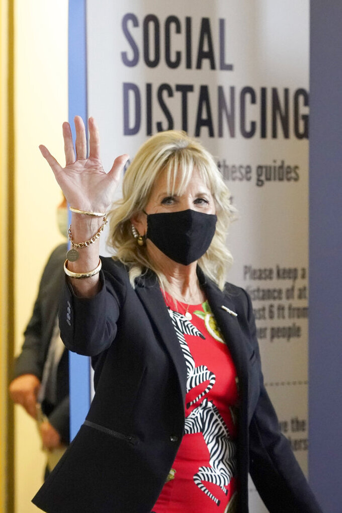 First lady Jill Biden waves to assembled local media as she makes her way past COVID education posters during a visit to vaccination site at Jackson State University in Jackson, Miss., Tuesday, June 22, 2021, as part of the Biden administration's nationwide tour to reach Americans who haven't been vaccinated and to promote vaccine education. (AP Photo/Rogelio V. Solis)