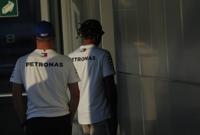 Mercedes driver Lewis Hamilton of Britain, right, and Mercedes driver Valtteri Bottas of Finland, left, walk together after attending a media conference prior to the Russian Formula One Grand Prix, at the Sochi Autodrom circuit, in Sochi, Russia, Thursday, Sept. 24, 2020. The Russian Formula One Grand Prix will take place on Sunday, Sept. 27, 2020. (AP Photo/Pavel Golovkin)