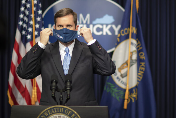 Kentucky Gov. Andy Beshear takes off his facial mask before providing an update on the COVID-19 pandemic in the state during a media conference at the Kentucky state Capitol in Frankfort, Ky., on Thursday, Jan. 21, 2021. (Ryan C. Hermens/Lexington Herald-Leader via AP)